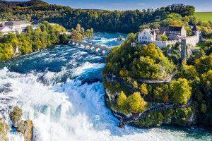 Rhine Falls or Rheinfall, Switzerland panoramic aerial view. Tourist boat in waterfall. Bridge and border between the cantons Schaffhausen and Zürich. Cliff-top Schloss Laufen castle, Laufen-Uhwiesen